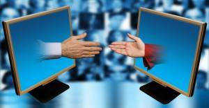 male and female hands reaching at each other against a backround with people faces, social network concept